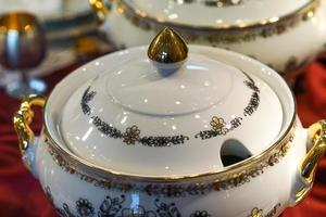 Background with white porcelain tableware with floral ornament and gilded details. photo