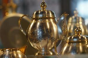 Silver teapot with blackened floral patterns on blurred background. photo