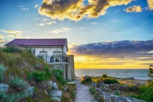 little house by the sea during sunset photo