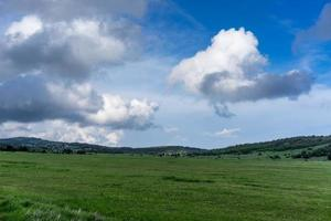 A huge green field of grass under blue sky and white clouds. photo