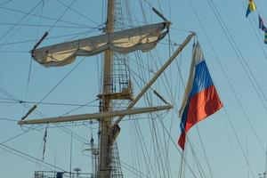 the mast of the sailboat and the Russian flag against the blue sky. photo