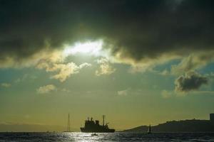 paisaje marino con una vista de la silueta de la ciudad y el barco foto