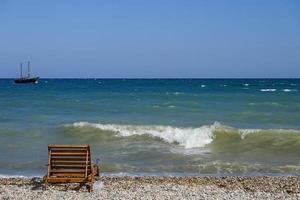 paisaje marino con un banco de madera y un barco en el horizonte. foto