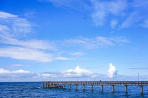 paisaje marino con vistas al largo muelle de la ciudad turística con gente caminando. foto