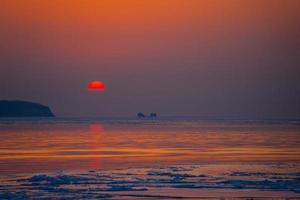 paisaje marino playa de hielo y la puesta de sol roja. foto