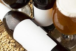 Botella de cerveza de maqueta sobre fondo de cebada foto