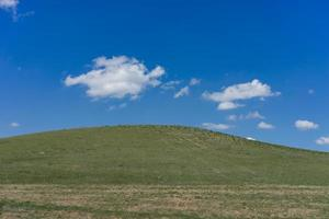 colina verde cubierta de hierba contra un cielo azul con nubes. foto