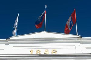 Flags on top of a white colonnade against a blue sky. photo