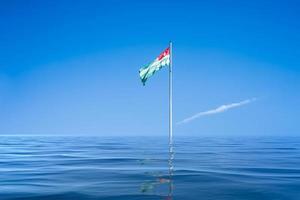La bandera de Abjasia en el fondo del cielo azul y las nubes foto