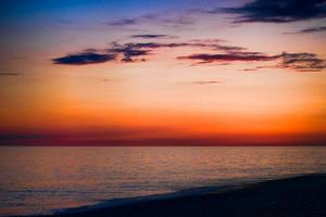 bright sunset over the blue sea with shimmering different colors in the clouds photo