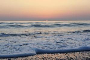 paisaje con olas de espuma blanca del mar en una playa de arena foto