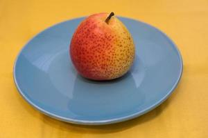 Juicy and bright pear on blue ceramic plate standing photo