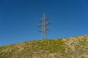 electric tower on a hill against a blue sky. photo