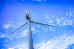 Wind power plant against a blue sky with white clouds photo