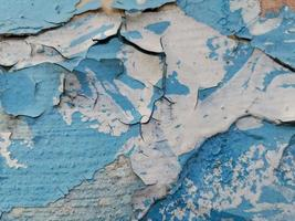 Blue background with cracked oil paint on plaster. photo