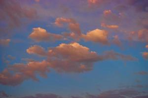 magical pink clouds at sunset on background of blue sky photo