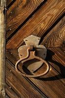 Rusty door handle on the background of the door of a wooden house. photo