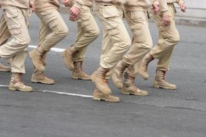 People in light military uniform are on the road systems photo