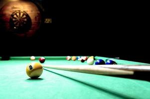 Billiard table and a dart boart on the wall photo