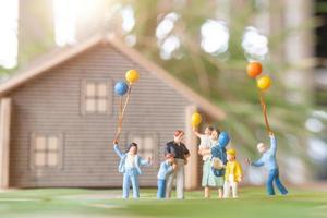 gente en miniatura, familia feliz jugando en el césped del patio trasero. concepto de vida en casa foto