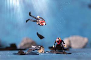 Gente en miniatura, buzos limpian la contaminación de basura plástica desechada en el océano, concepto de contaminación submarina foto