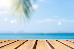 El enfoque selectivo de la mesa de madera vieja con una hermosa playa borrosa con palmeras tropicales para mostrar su producto. foto