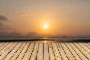 Selective focus of old wood table with a blurred beautiful beach to display your product. photo