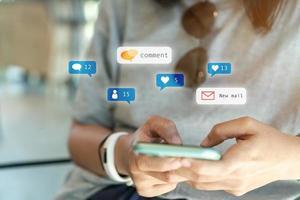 mujer sosteniendo un teléfono inteligente para usar las redes sociales con iconos de comunicación. concepto de tecnología. foto