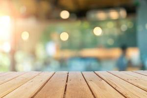 Selective focus of wooden table with a blurred coffee and restaurant cafe with customers background. photo