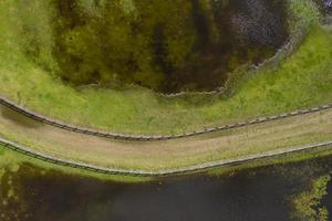 Drone aerial photograph of a horse trotting track near a fresh water lake photo