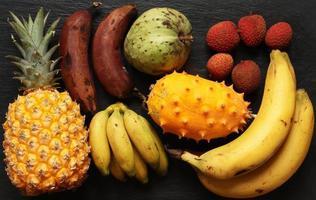 Foto de varias frutas tropicales sobre fondo de pizarra para ilustración de alimentos