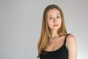 Portrait of an attractive teenage girl wearing a camisole posing looking at the camera on a grey background photo