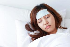 Young Asian woman is sick and sleeping in bed. photo