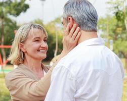 pareja senior sonriendo y de pie haciendo contacto visual en el parque felizmente. foto