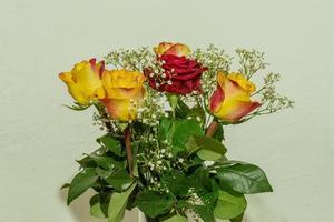 Hermoso ramo romántico de rosas amarillas y rojas con hojas verdes. foto