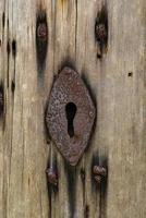 Viejo oxidado ojo de la cerradura en una antigua puerta de madera foto