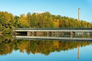 Vista otoñal de un puente bajo que cruza un río en Suecia foto