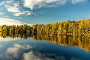 Árboles de colores otoñales a lo largo de la orilla de un río en Suecia foto