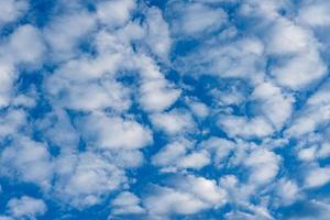 Blue sky background with fluffy white clouds photo