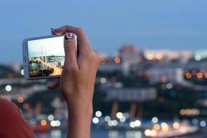 Girl's hand with a smartphone taking pictures of the Golden bridge. Vladivostok, Russia photo