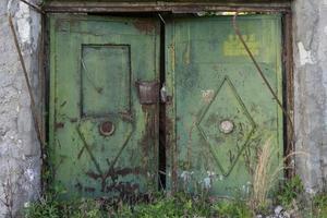 Puerta de metal antiguo en el fondo de una pared de ladrillo gris. foto