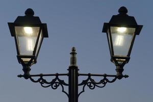 luces eléctricas en estilo antiguo con el paseo marítimo de sochi en la noche foto