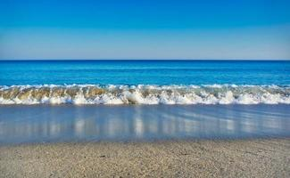 Seascape with clear blue sea, cloudless sky and white sandy beach photo