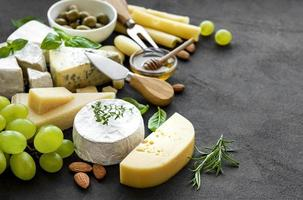Various types of cheese, grapes, honey, and snacks on a black concrete background photo