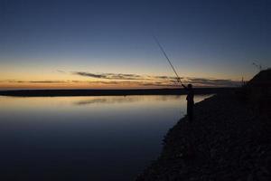 paisaje marino con la silueta de un pescador foto