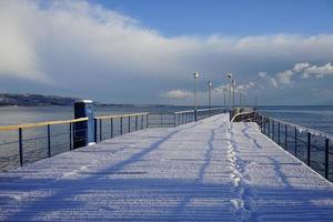 Muelle de barcos marinos en un país subtropical bajo una capa de nieve foto