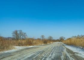 camino rural en el fondo de un paisaje invernal. foto