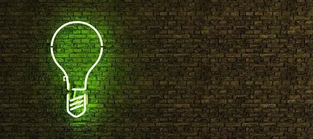 Green neon lamp with light bulb symbol on brick wall with copy space photo