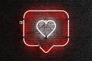Red neon notification frame with heart inside on brick wall photo