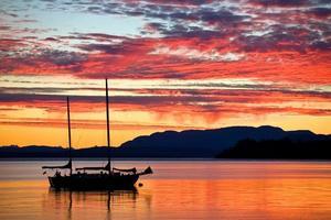 Velero al atardecer en la costa oeste de Columbia Británica foto